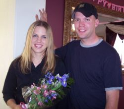 A man's hand seems to come out of his fiancee's head as she laughs and holds flowers