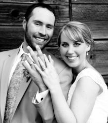 An ecstatic newly engaged Christian single shows off her wedding ring next to her husband