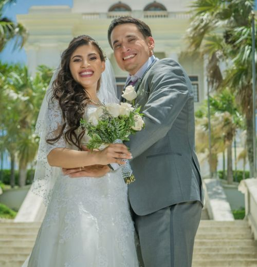 US Christian single poses after marrying Dominican wife who is holding bouquet