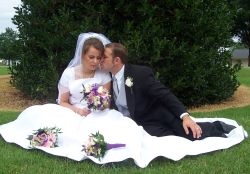 A beautiful bride sits on the grass with her husband who kisses her