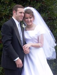 Excited Christian couple hold hands and lean in close together after marrying