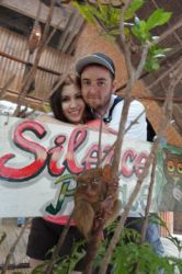 A couple embrace in front of a sign which says Silence