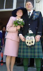 Romanian Christian marries a man in a kilt as they pose outside together full of smiles
