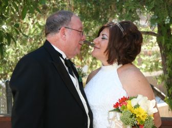 A former single Christian from California smiles with eyes closed as her new husband leans in to kiss her