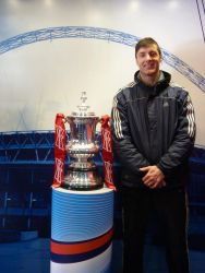 A man stands next to the FA Cup