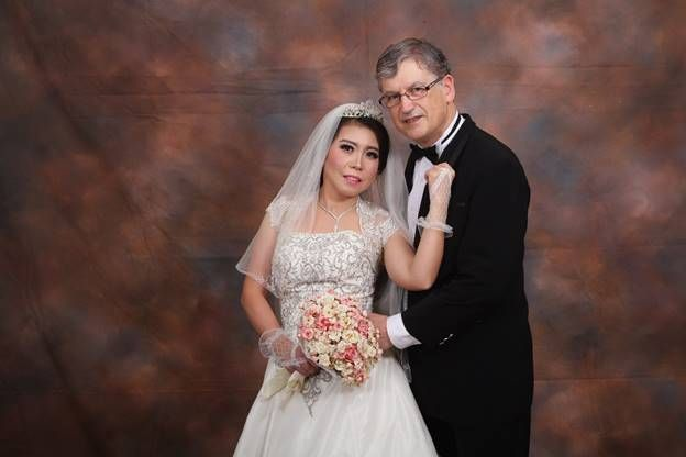 Christian senior marries Indonesian bride who tenderly holds onto him in her white wedding dress