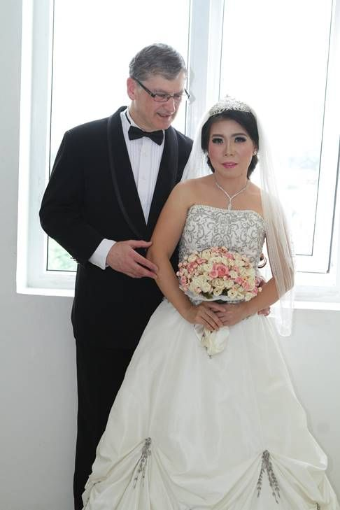 Madly in love White man tenderly talks to his beautiful Asian bride who holds bridal bouquet