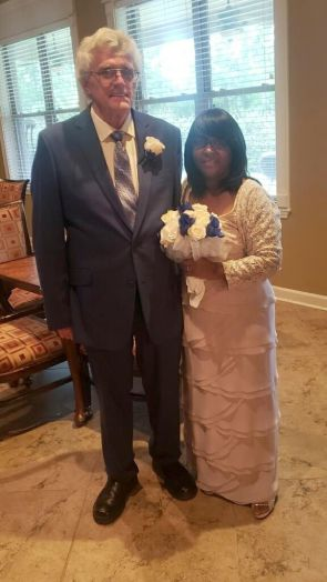 Senior Christian singles pose, with bride in rose dress and holding bouquet of flowers