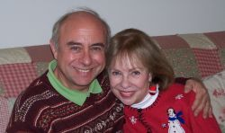 Senior Christians cuddle on the couch and smile in the wintertime