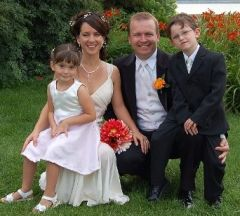 New life for blended Christian family who pose at outdoor wedding