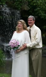 A man lovingly holds his wife from behind, with a waterfall in the background