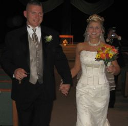 A beautiful bride holding flowers in one hand and her lucky husband in the other smiles