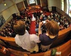 A Christian couple stand in a church and take a picture while in the background their friends marry