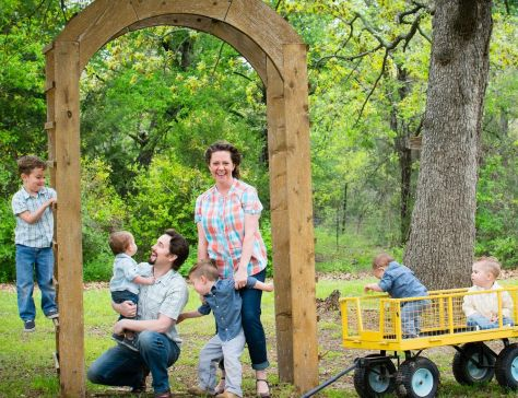 Married couple stand and laugh while holding their children under their wedding arch