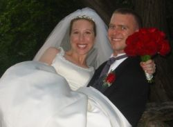 A strong groom carries his beautiful and joyful Christian bride
