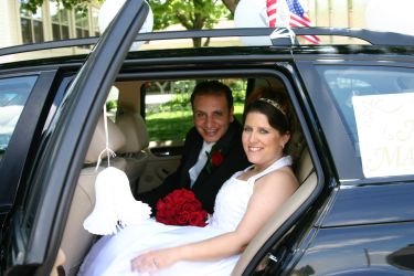 A beautiful bride sits with her new husband in the wedding car