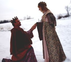 A king on one knee asks for a queen's hand in marriage in the snow