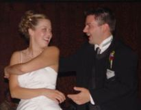 A bride has her hands wrapped around herself trying to grab her husband as they laugh