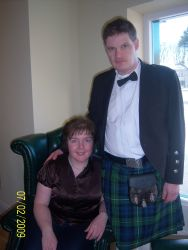 English Christian engaged in Northern Ireland. A man in a kilt stands next to his seated wife