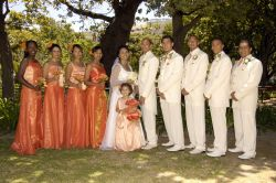 Bridesmaids in orange and groomsmen in white flank the happy married couple
