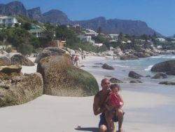 A man kneels down on the sand with his daughter while at the beach