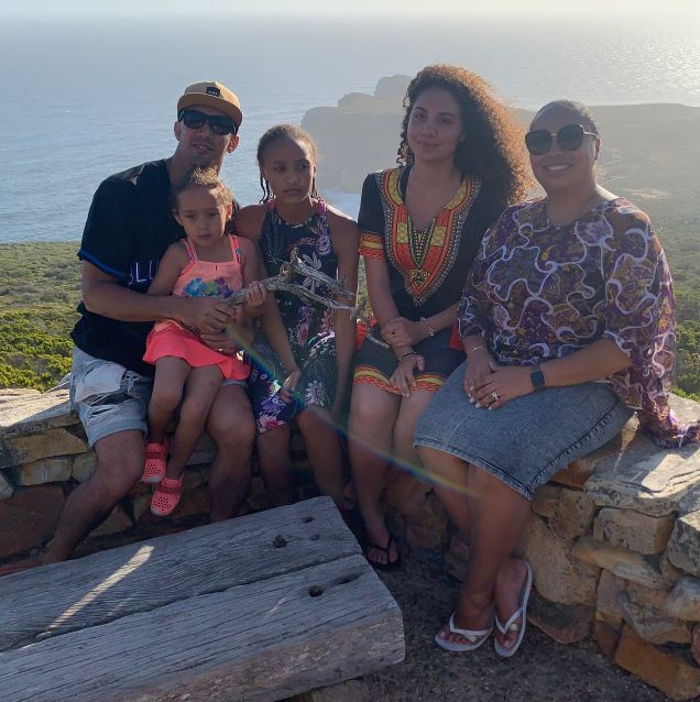 Family looking at camera with ocean and hills in background
