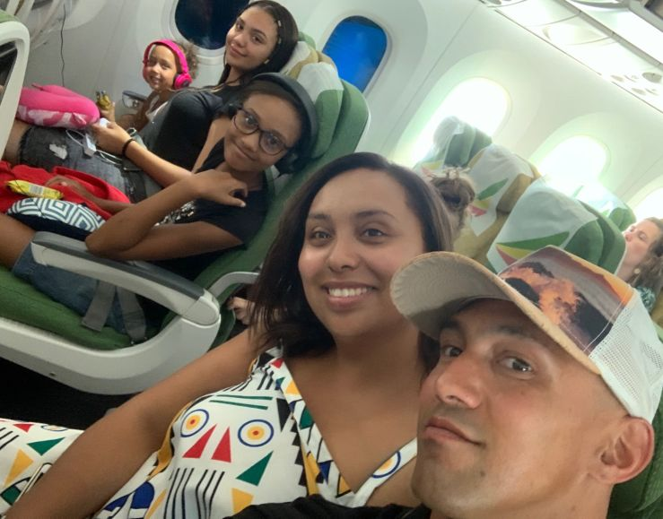 Selfie on plane showing parents and 3 children in background