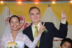 A smiling married couple give the peace sign while laughing together