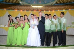 A beautiful bride in white stands next to her husband and her bridal party
