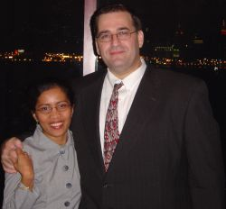 A tall man hugs his wife at night
