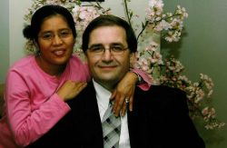 A woman in pink wraps her arms around her smiling man