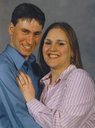 A Christian woman affectionately puts her hand on a laughing man as he hugs her