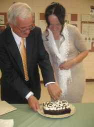 A man cuts a piece of cake for a beautiful woman