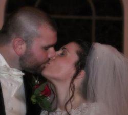 Christian bride and groom lovingly kiss