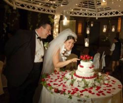 A bride playfully tries cutting the wedding cake with her finger while the groom laughs