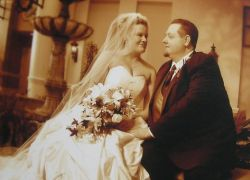 Newlywed Christians stare intently at each while seated hand in hand