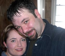 Man with goatee leans his head into a pretty woman, who smiles
