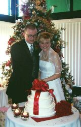 Happy couple cut wedding cake in front of Christmas tree