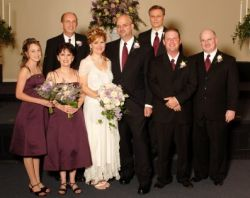 Bridesmaids and groomsmen surround a beaming newly married Christian couple