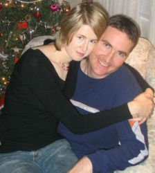 An ecstatic man smiles as his Canadian Christian fiancee sits on his lap at Christmas