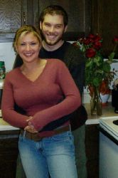 A man hugs a beautiful woman who smiles in the kitchen