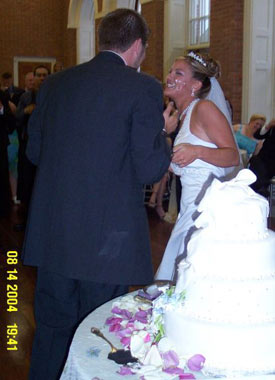 Laughing bride tries in vain to avoid getting wedding cake on her face