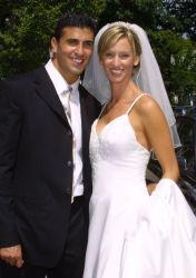 Attractive Christian couple from NY smile together at their outdoor wedding