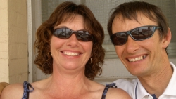 A couple wearing matching sunglasses look very at ease together