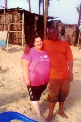 An interracial couple smile arm in arm on the beach