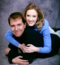 Pretty Christian woman tackles a man by wrapping her arms around him. He smiles.