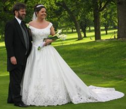 A pretty Christian bride in a beautiful wedding dress poses on the grass with her new Christian husband