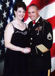 Christian army man holds hands with a beautiful woman in front of large American flag