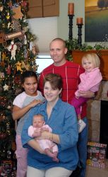 Christian parents pose by the Christmas tree holding their 3 children