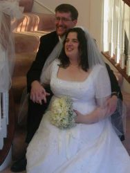 Nova Scotia Christian bride sits on the stairs with her new husband who holds her hand